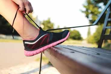 Rituale um Sport zu betreiben. Frau zieht Turnschuh an.