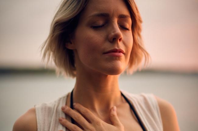 Eine Frau praktiziert Selbstfürsorge am Strand