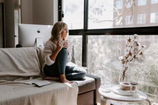 Eine Frau sitzt im Wohnzimmer und denk über die Corona Krise nach