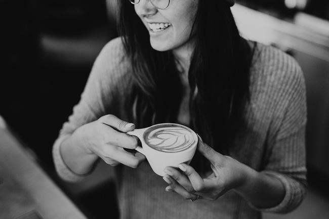 Eine Frau trinkt Kaffee und ist durch gute Gedanken glücklicher
