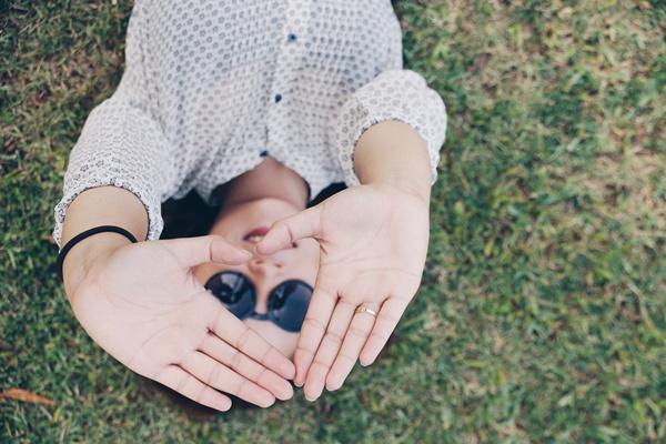 Eine Frau liegt in der Wiese und macht eine Selbtliebe-Übung