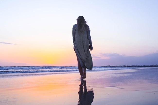 Eine Frau spaziert am Strand und folgt ihrer Intuition