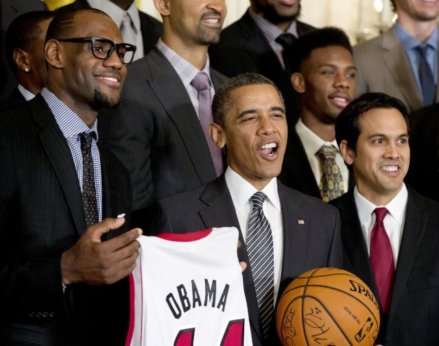 Two members of the Black bourgeoisie - LeBron James poses next to Barack Obama while holding an Obama basketball jersey.