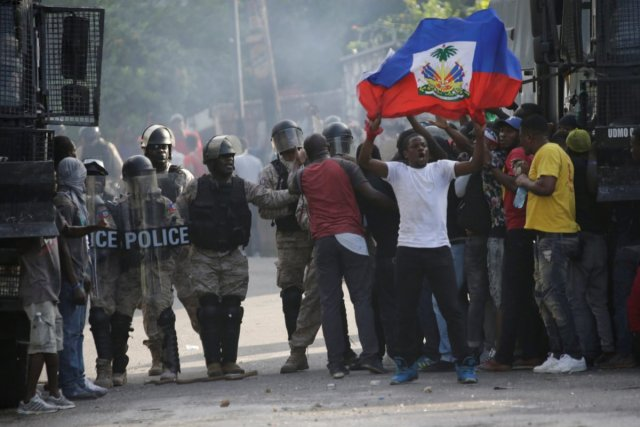 Protesters try to pass the police cordon during a demonstration to demand the resignation of Haitian president Jovenel Moise, in the streets of Petion Ville, Port-au-Prince