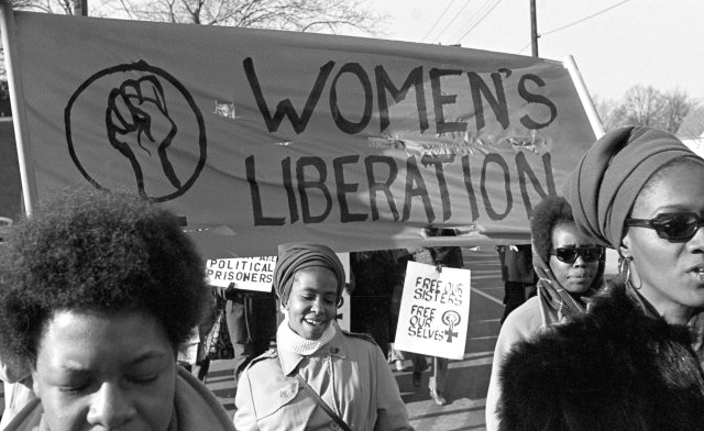 "African women gathered in a front of a banner that says ""Women's liberation"""