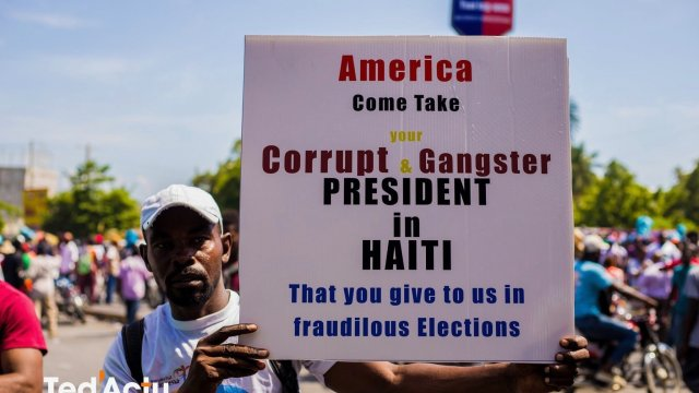 A protester holds a sign calling out US imperialism at a demonstration inHaiti