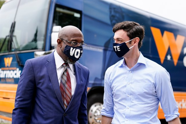 """Democratic candidate for Senate Jon Ossoff, right, and Democratic candidate for Senate Raphael G. Warnock, left, arrive before they speak to a crowd during a """"Get Out the Early Vote"""" event at the SluttyVegan ATL restaurant on Tuesday, Oct. 27, 2020, in Jonesboro, Ga. (AP Photo/Brynn Anderson)"""