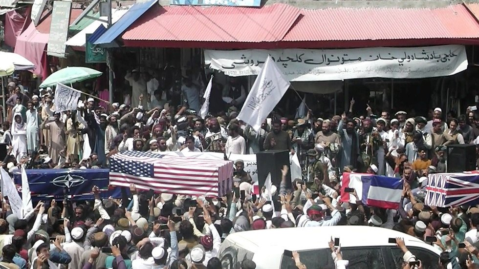 Afghan crowd carries makeshift coffins draped in NATO, US and UK flags during a pretend funeral on a street in Khost, Afghanistan August 31, 2021. © Reuters / ZHMAN TV