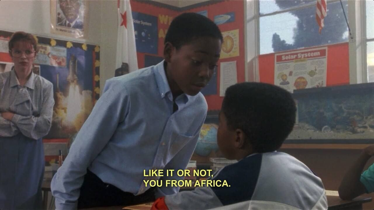 """An African student stands over another and says """"like it or not, you're from Africa."""""""