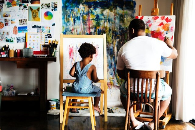 An African parent and child paint