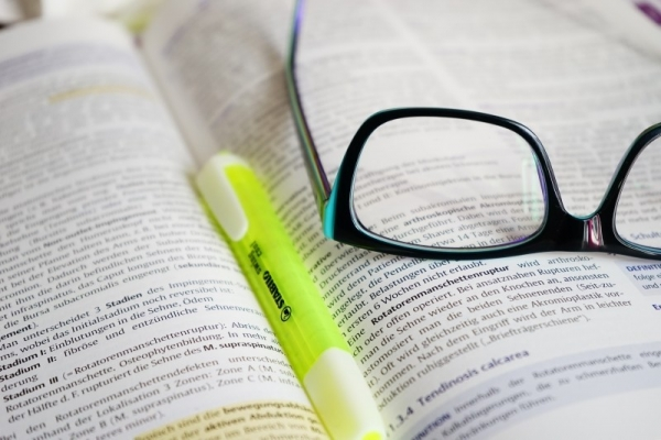 eyeglasses-and-highlighter-on-open-book