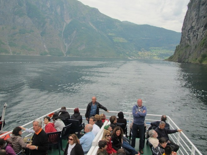On the open deck of the boat, cruising down the fjord