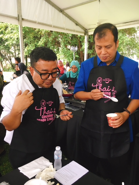 Chef Korn and Ahman Mad-adam, Director of Tourism Authority of Thailand (Malaysia & Brunei) tasting the food at a cooking station