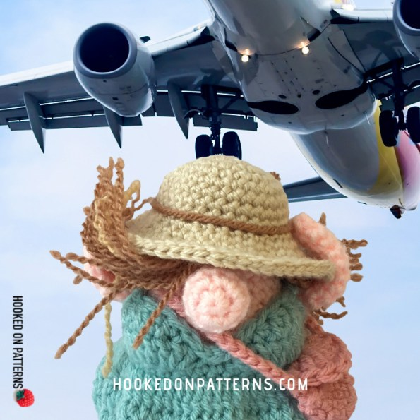 A posed image of Eve Gonk in her tourist outfit under an airplane