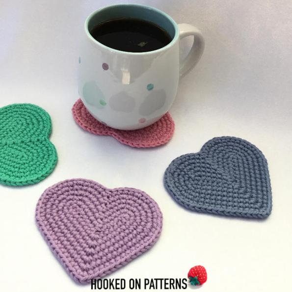A photo of 4 heart shaped crochet coasters made in pastel colours with a white mug featuring multicolour polka dots.