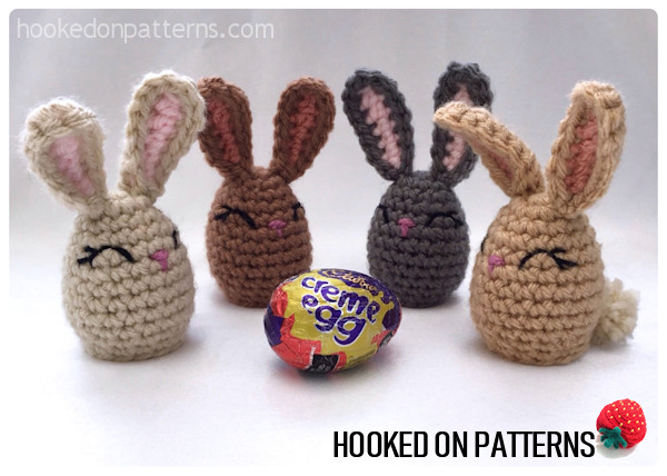 A photo of 4 completed crocheted Bunny Creme Egg covers displayed with a Cadbury's Creme Egg