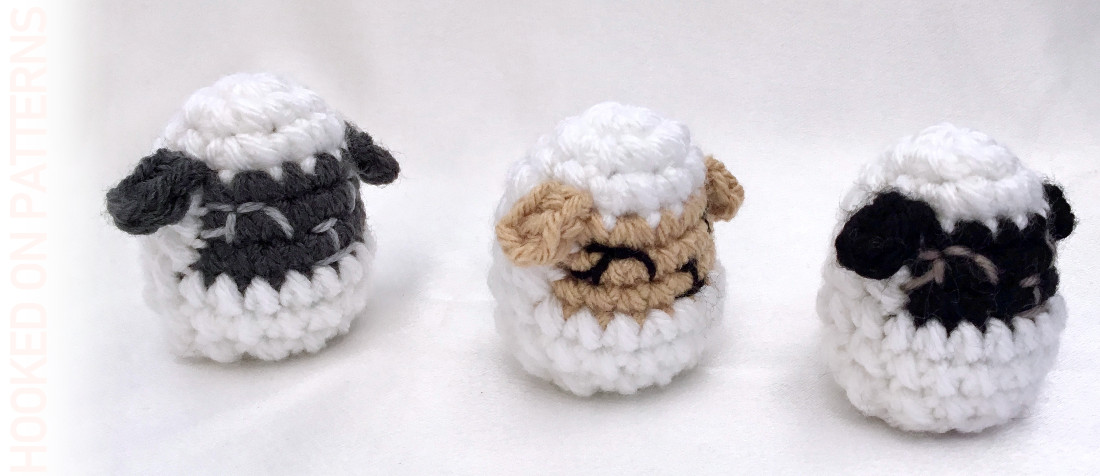 A close up photo of 3 crocheted Easter egg shaped lambs