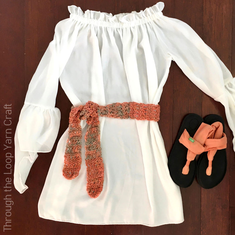 A photo of a white blouse with an orange coloured crochet belt wrapped around it