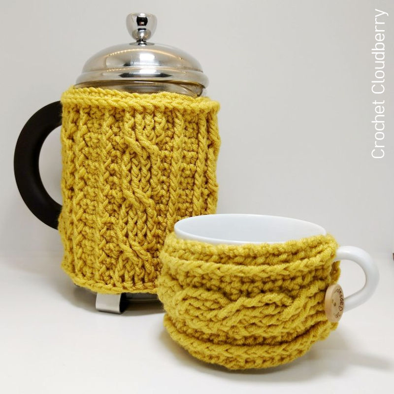 A photo of a mustard yellow coloured cafetiere crochet cosy with a matching mug cosy.