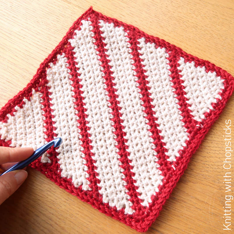 A photo of a crochet square with red and white diagonal striping