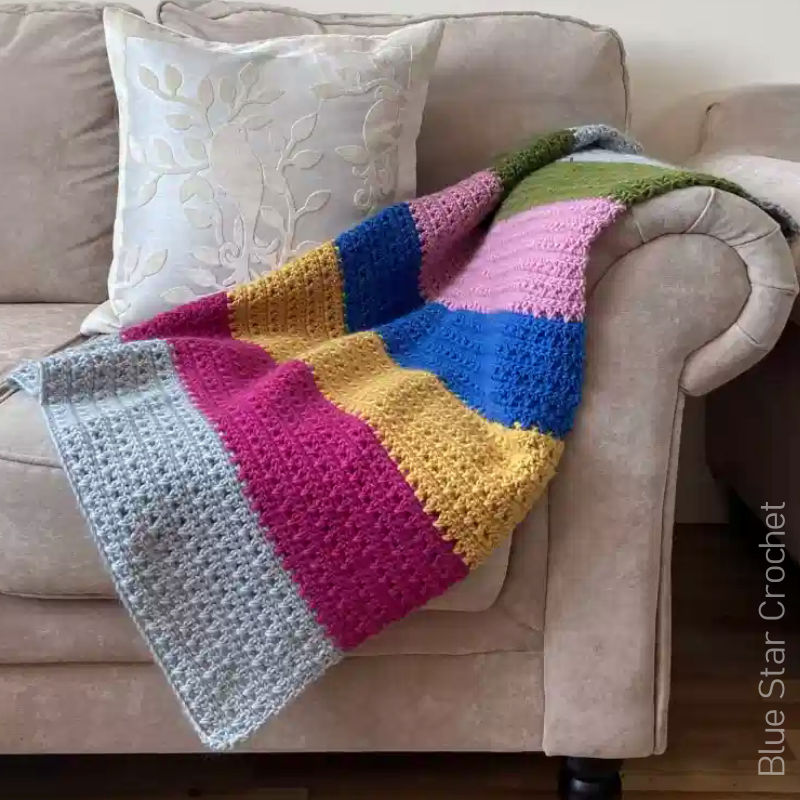 A photo of a multicoloured thick striped, textured, crochet blanket laying on a couch.