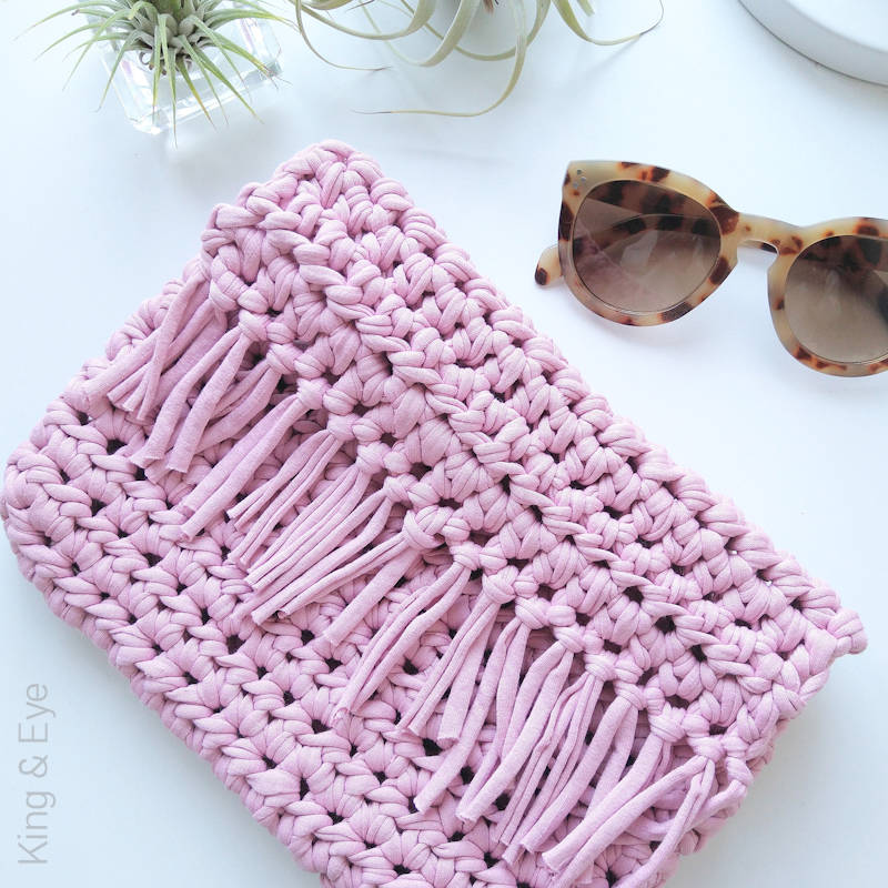 A photo of a chunky, boho style, pink crocheted clutch bag with tassels