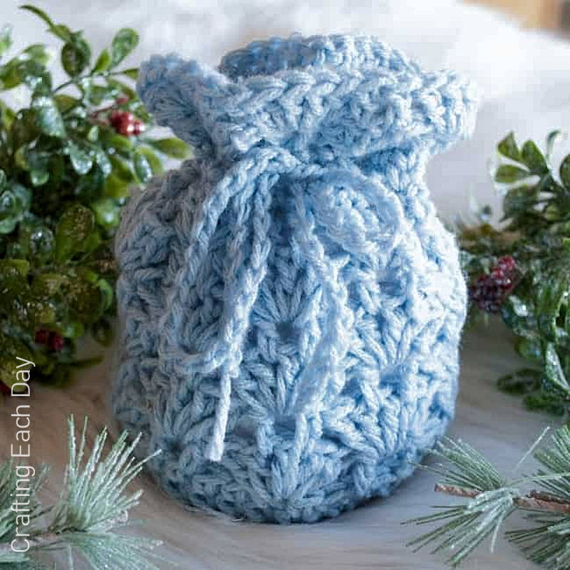 A close up photo of a light blue crocheted gift bag with a shell stitch pattern design