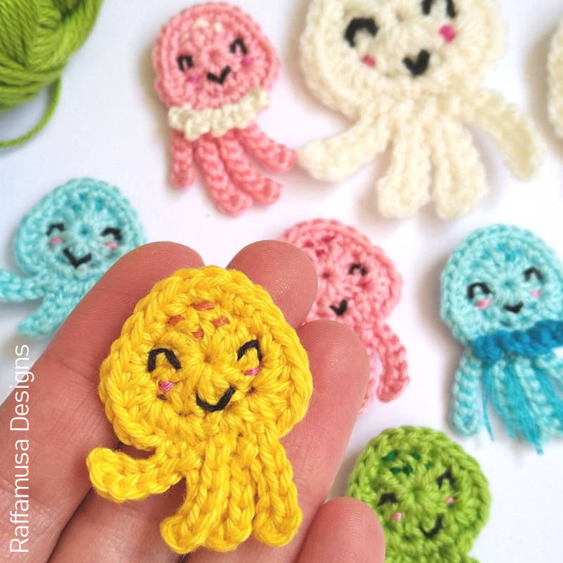 A photo of a hand holding a small jellyfish crochet applique with more in the background