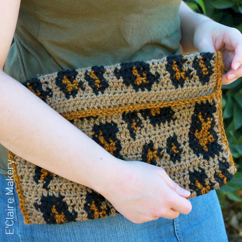 A photo of a person holding a crocheted clutch bag featuring a leopard skin style design
