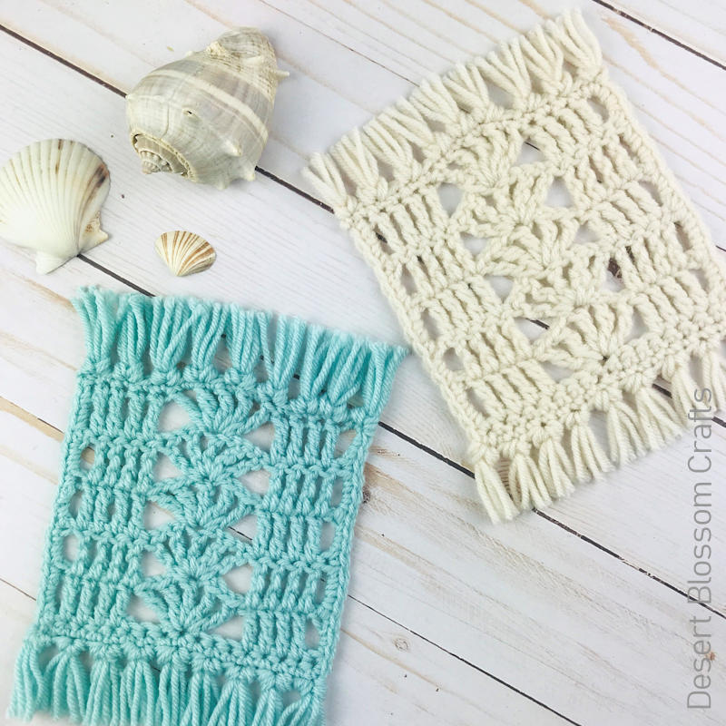 A photo of 2 lacy shell stitch crocheted mug rugs, one in blue, and one in white