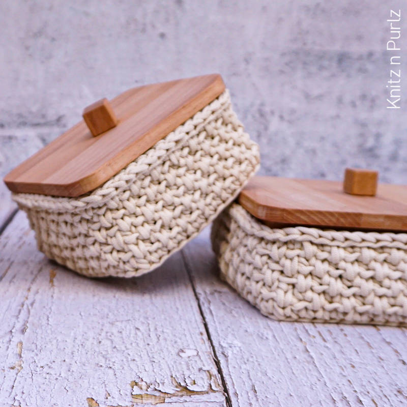 A photo of a couple of crocheted baskets with wooden lids.