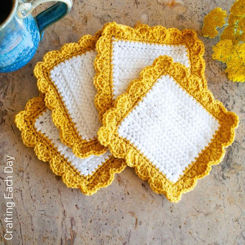 A photo of 4 white square crocheted coasters with golden yellow shell stitch borders - A completed scrap yarn project.