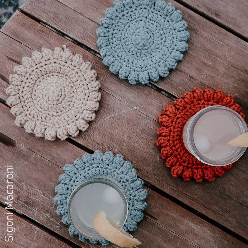 A photo showing 4 crocheted coasters on a wooden table