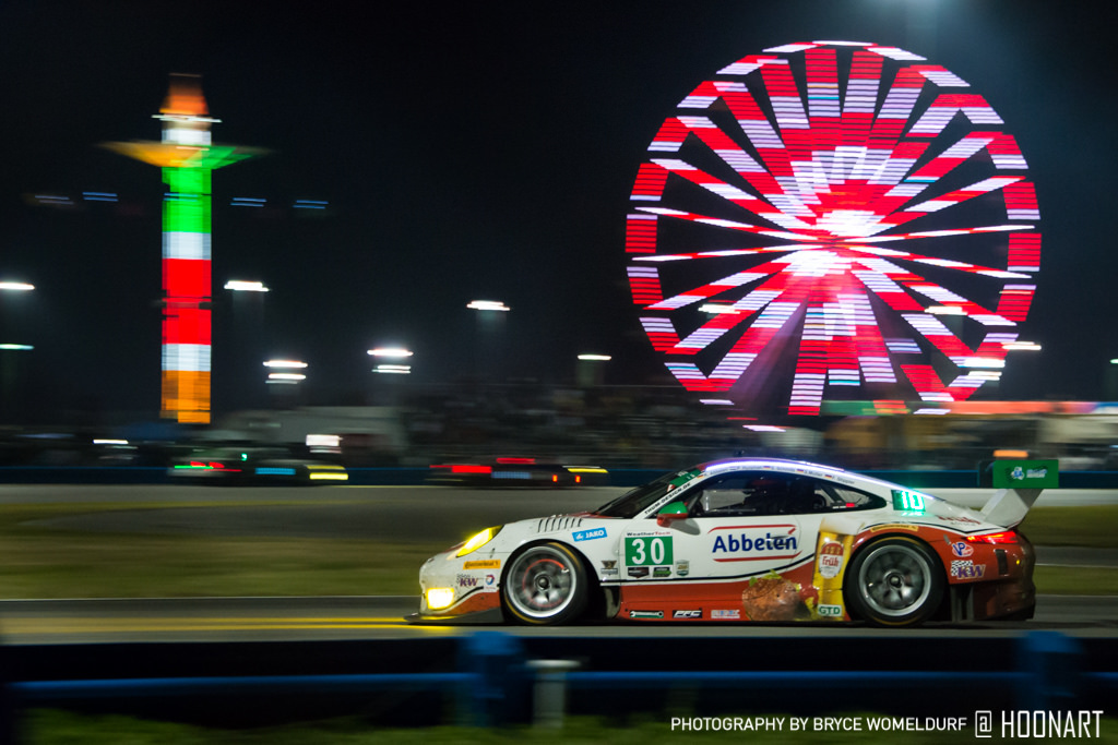 Number 30 car zooming past the ferris wheel at the Rolex24 in Daytona