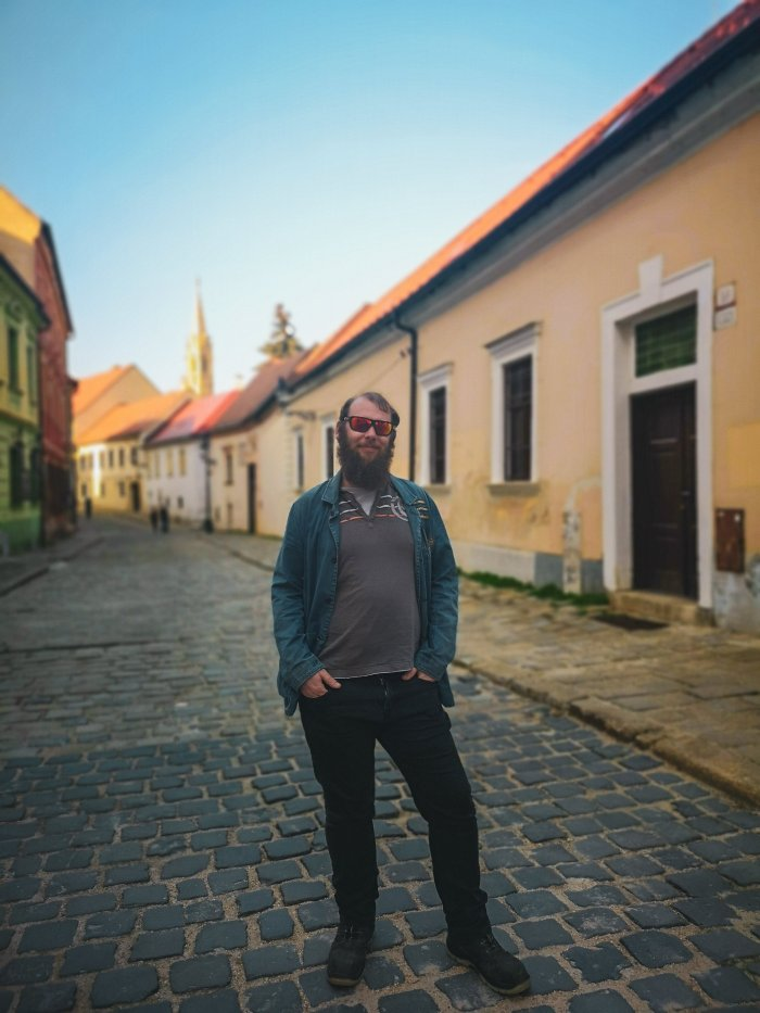 Henry standing on an old cobbled street with pastel buildings-Bratislava-First-Timer's-Guide-Local-Guide-Hoopla-Adventures