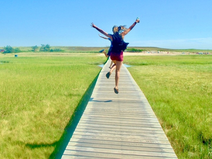 Young girl jumping in the air on a boardwalk in the marsh