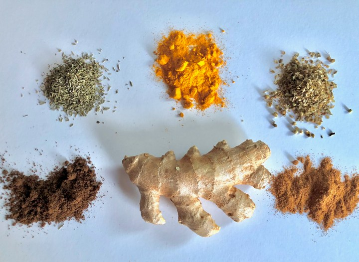 piece of fresh ginger surrounded by spall piles of various spices