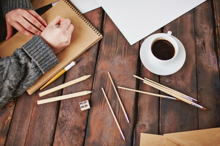 Image of cup of coffee and objects for hand drawing and male hands over notepad