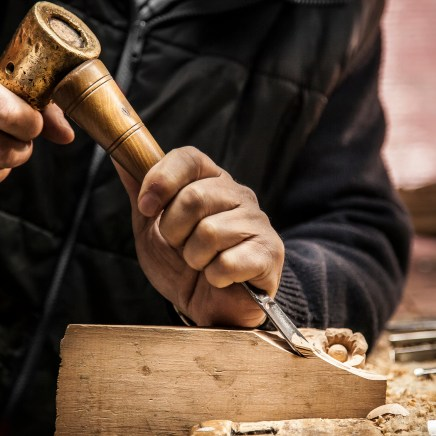 An engraver is carving a piece of wood frame