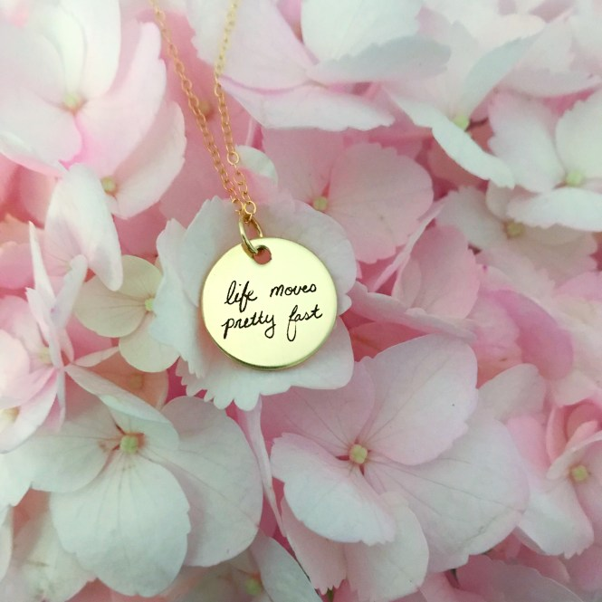"Gold Necklace with ""life moves pretty fast"" written on circle disk in front of pink hydrangeas"