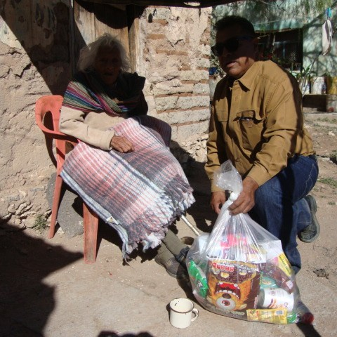 Teodora Escalante, sits in a chair all day under a homemade porch made of blankets. She lives in an adobe hut. She believes in Christ and God, wants to go to church but does not have enough strength walk 5 blocks, believes in Jesus and God.