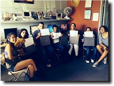 Computer class graduates with diplomas and free laptop computers