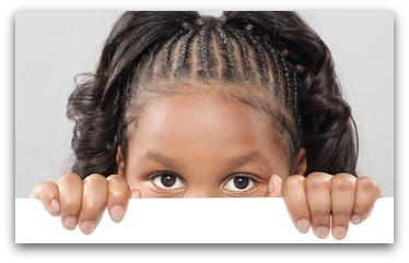 Little girl peeking from behind copy space