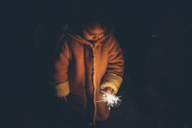 Child with sparkler at night