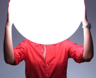 young casual woman covering her ears over a shiny blank circle. hear no evil concept. on gray background