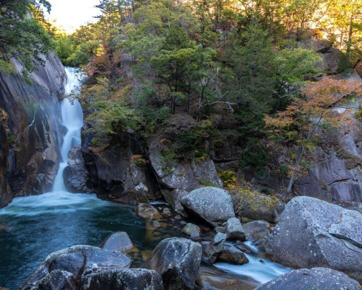 Witnessing the Mitake Shosenkyo Gorge waterfall during autumn season is a spectacular sight to see.