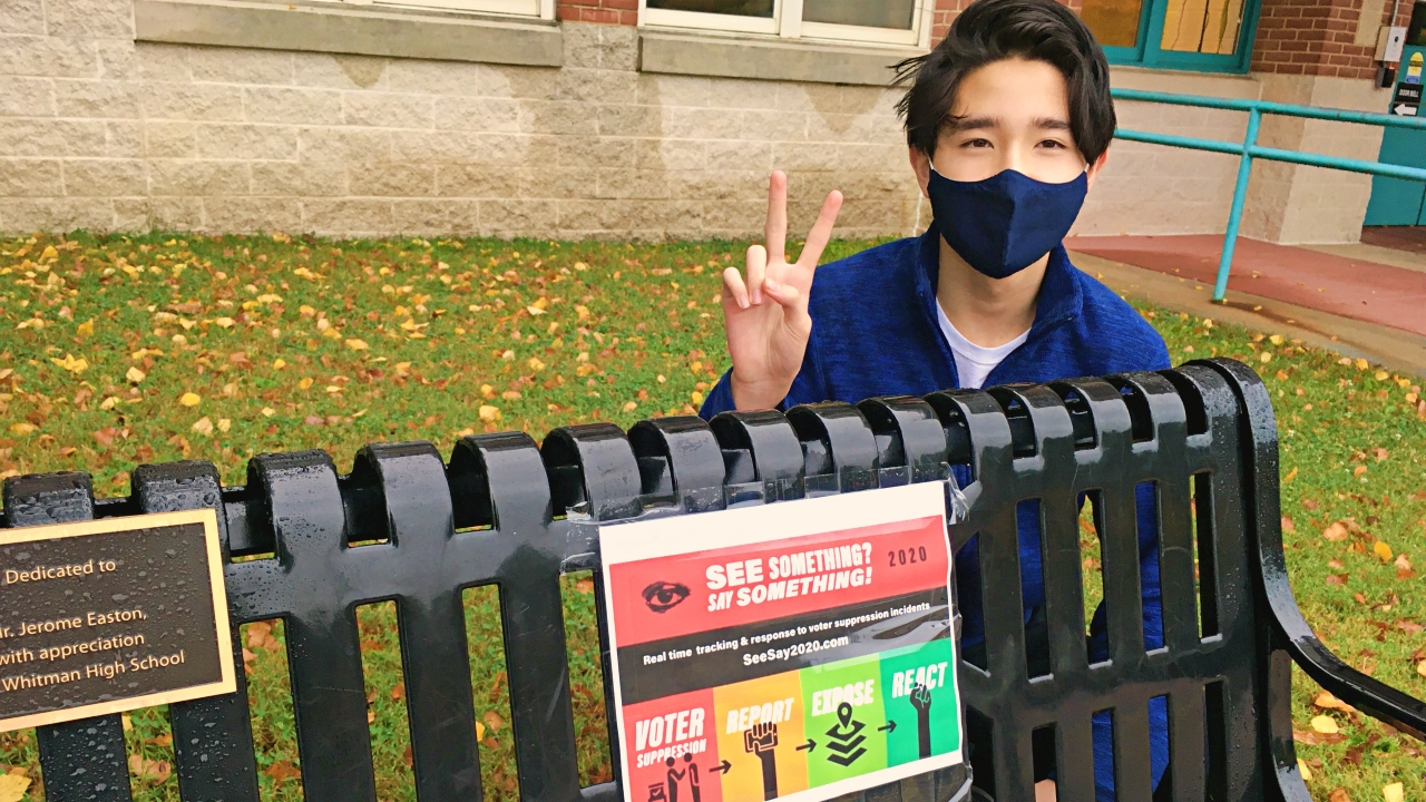 Student posting in front of voting sign