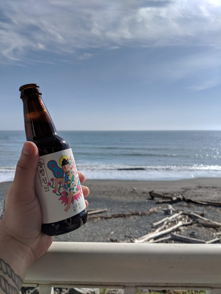 Hand holding a bottle of The Booth red ale against a deck rail, overlooking a southern Oregon coast beach.