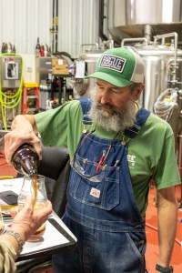 John Maier pouring a sample of a pilot beer he's working on.