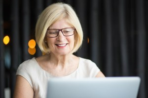 Closeup of Smiling Senior Woman Working on Laptop